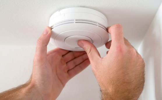 Person testing smoke alarm