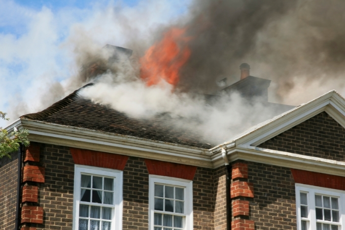 Brick house with roof on fire and smoke covering sky