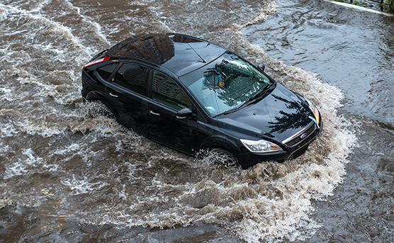 Black car driving through flood waters