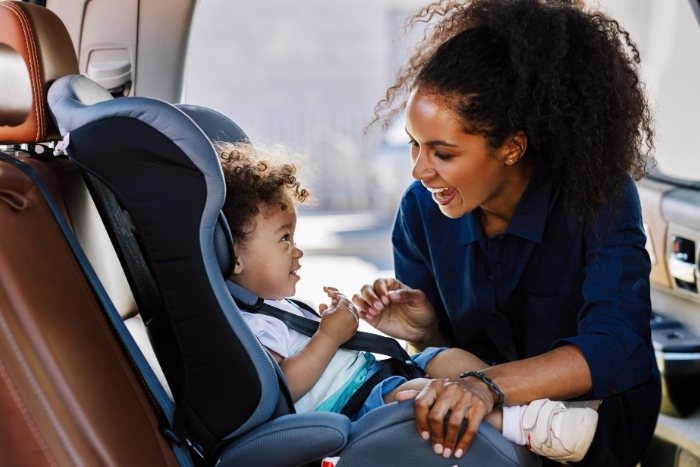 Woman placing child into car seat