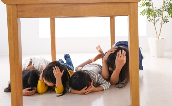 Family covering their heads while huddling under a table during earthquake