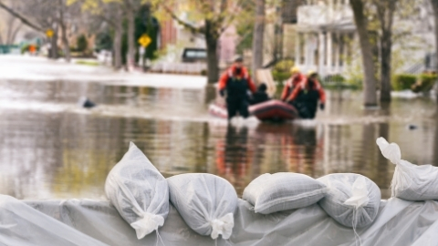 Flooded houses surrounded by sandbags with flood rescue raft transporting people