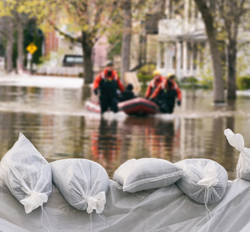 Sandbags surround flood waters as a rescue team pulls a raft of evacuees to safety