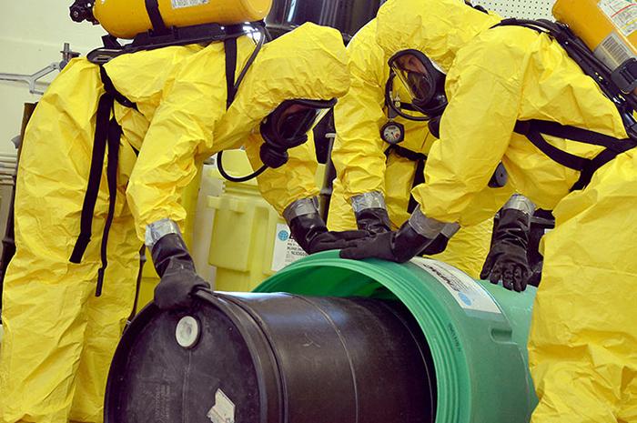 Workers in HazMat suits handle toxic chemicals in barrels