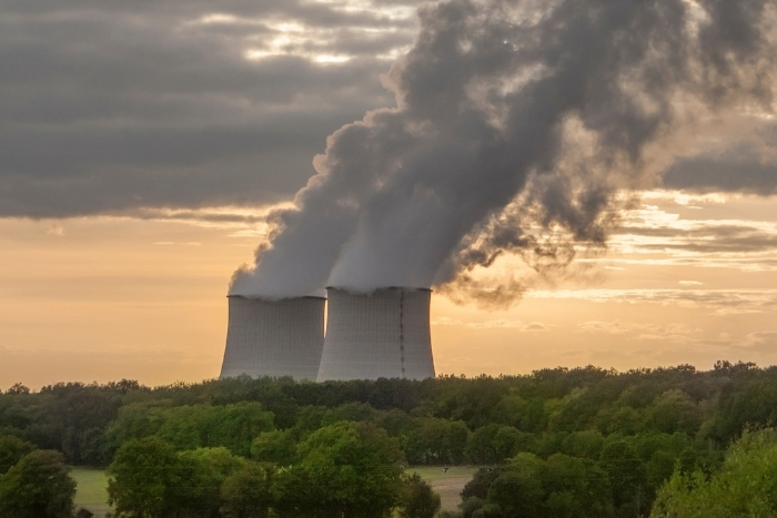 Nuclear Power plant with smoke rising into the sky surrounded by trees
