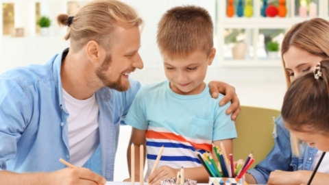 Father talking to son while drawing at the table with the mother and sister