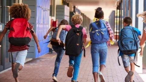 Kids running down school hallway