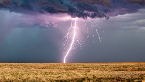 Severe thunderstorm with lightning striking a field