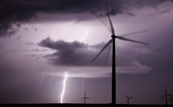 Lightning strikes at night amidst Iowa wind turbines