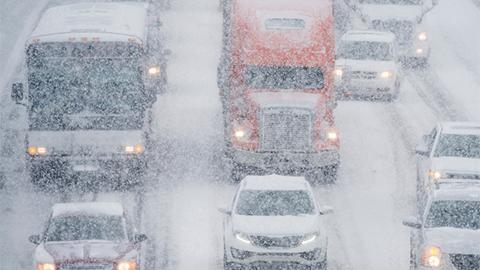 Vehicles driving through intense snow on interstate