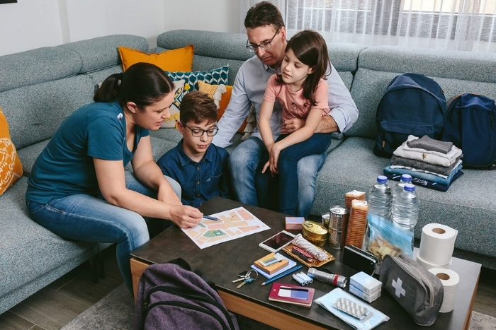 Family building an emergency supply kit and going over evacuation routes