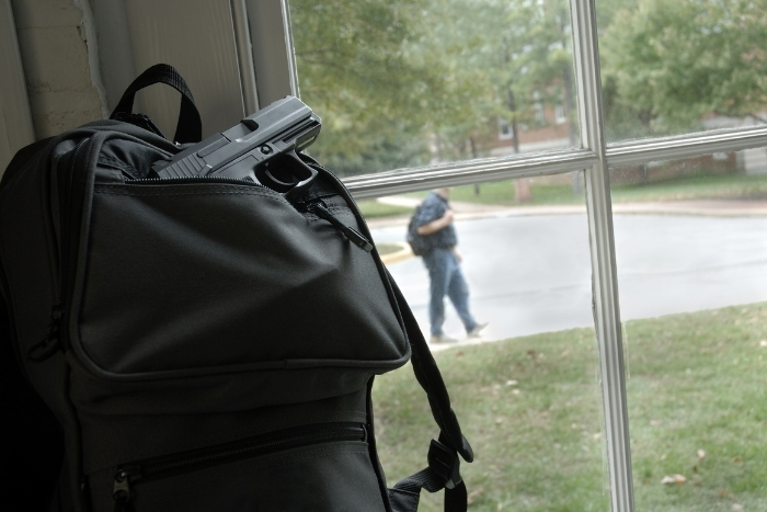 Backpack with gun sits by window with people walking by outside