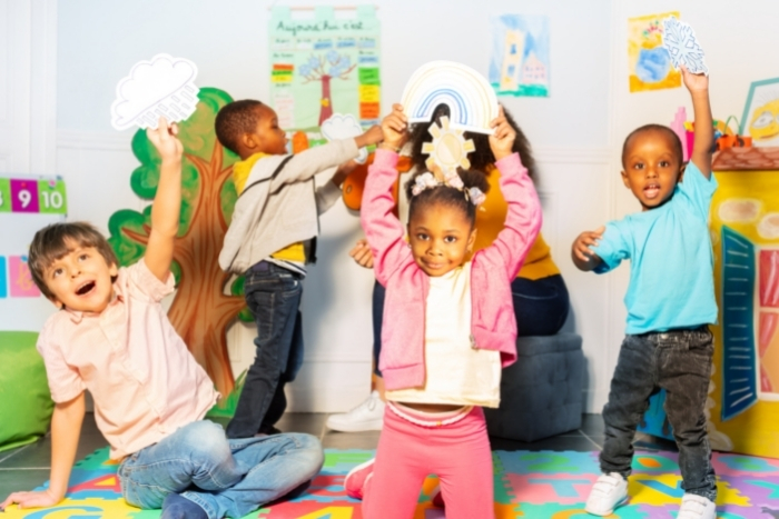 Young kids holding up weather-related drawings in classroom