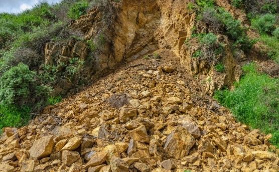 Rocks and dirt are sliding down hill during landslide